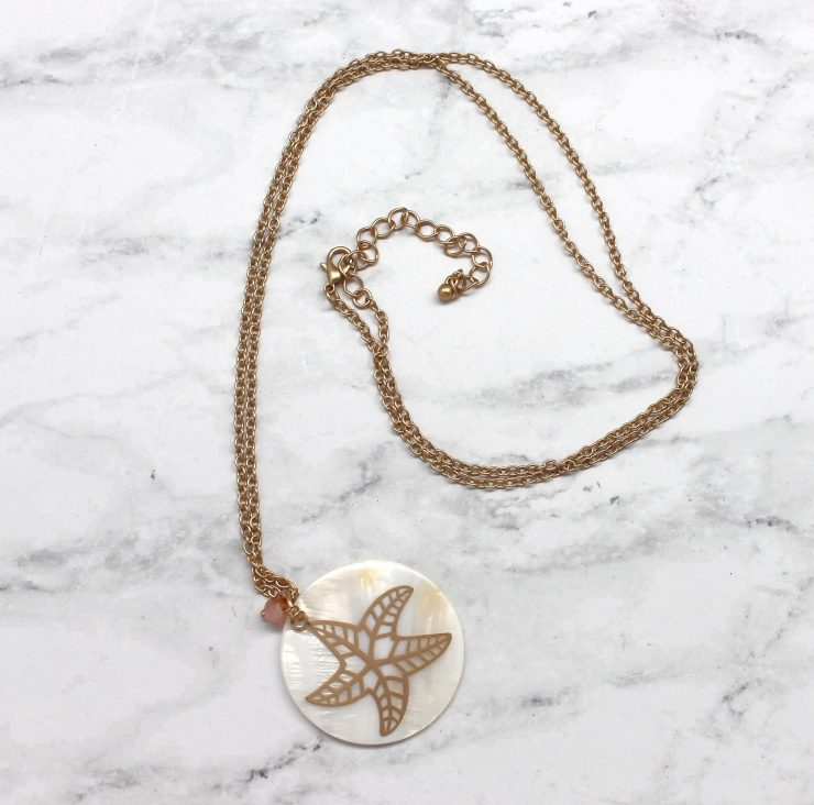 A photo of the Starfish On A Shell Necklace product
