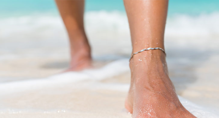 Photo of anklet on a person's ankle standing in sand and water