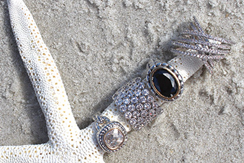 Photo of men's rings on starfish on sand