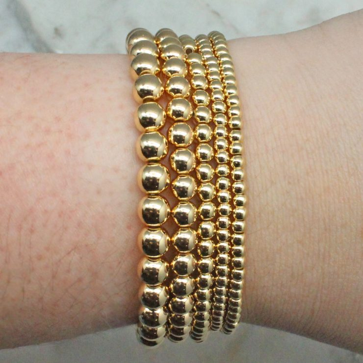 A photo of the Gold Beaded Stackable Bracelets - Set of 5 product