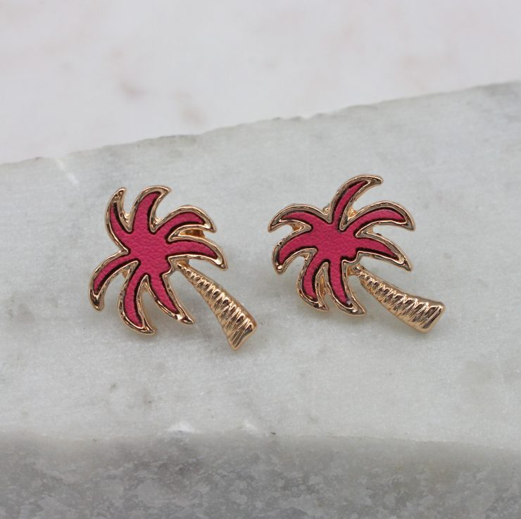 A photo of the Crescent Palm Earrings In Pink product