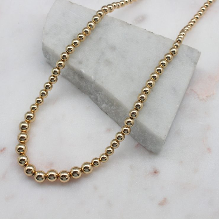 A photo of the Graduated Gold Beaded Necklace product