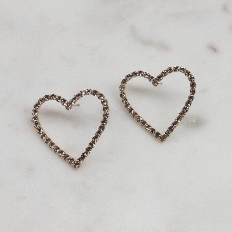 A photo of the Rhinestone Heart Earrings In Gold product