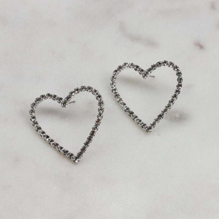 A photo of the Rhinestone Heart Earrings In Silver product